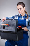 Woman opening a toolbox. Female manual worker opening a toolbox Royalty Free Stock Photography