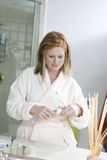 Woman Opening Toothpaste In Bathroom Stock Photos