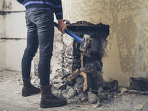Woman Opening Up Fireplace With Sledge Hammer Stock Photo