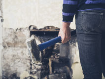 Woman Opening Up Fireplace With Sledge Hammer Royalty Free Stock Photography