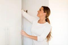 Woman opening wardrobe doors. Attractive woman opening wardrobe doors Royalty Free Stock Images