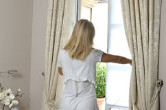 Woman Opening Window. Blonde woman in cozy home wear moving curtains and opening bedroom window Royalty Free Stock Photos