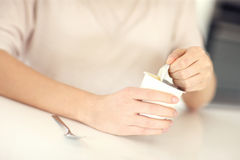 Woman opening yogurt Stock Photography