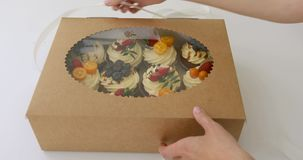 Hands open a box of cupcakes stock video