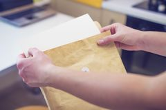 Woman opens brown envelope. brown crumpled paper envelope in hands of female on office background.  Royalty Free Stock Photography