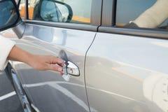 Woman opens car door close up Stock Images