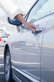 Woman opens car door Royalty Free Stock Photo
