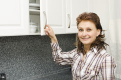 Woman opens a cupboard Stock Images