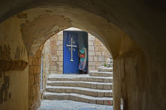 The woman opens the door into the Church of Jesus in the ancie Royalty Free Stock Photo