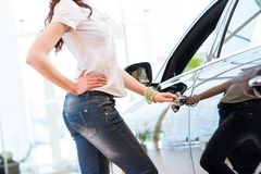 Woman opens the door to a new car Stock Photos