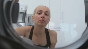 The woman opens the door of the washing machine and puts her dirty things. stock footage