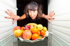 Woman opens the fridge with fruit. Woman opens the fridge and she is happy to see fruits stock photo