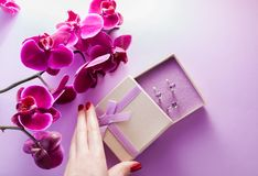 Woman opens a gift box with a set of amethyst jewellery surrounded with orchid. Woman opens a gift box with a set of amethyst jewellery with purple orchid Stock Image