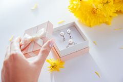 Woman opens a gift box with a set of pearl jewellery surrounded with flowers. Woman opens a gift box with a set of pearl jewellery with yellow flowers Stock Images