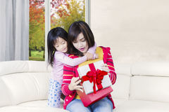 Woman opens a gift with her daughter Royalty Free Stock Photo