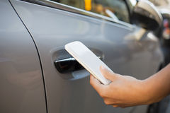 Woman opens her car with her mobile phone Stock Photos