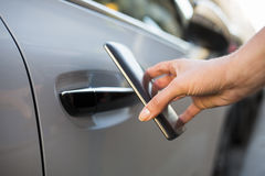 Woman opens her car with her smart phone Stock Photos