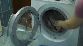 Woman opens the lid of the washing machine. She takes a clean wet laundry from the washing machine. Woman closes the lid of the washing machine stock video