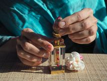 A woman opens the perfume oil. Scented oil in women`s wrists. Arabian perfume oil. A woman opens the perfume oil. Scented oil in women`s wrists Royalty Free Stock Photos