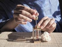 A woman opens the perfume oil. Scented oil in women`s wrists. Arabian perfume oil. A woman opens the perfume oil. Scented oil in women`s wrists Stock Image