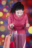 Woman opens shopping bags with christmas background. Happy indian woman wearing winter clothes and opens shopping bags with christmas background Royalty Free Stock Photo