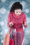 Woman opens shopping bags with winter background Stock Photo