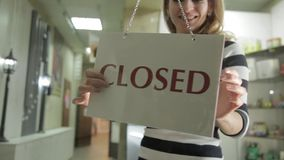 Woman opens store and flipping nameplate with closed sign