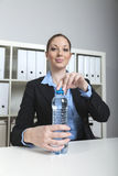 Woman opens water bottle in office Stock Photography