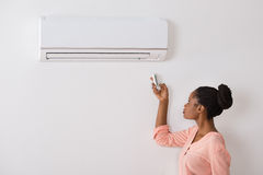 Woman Operating Air Conditioner With Remote Control Royalty Free Stock Photography