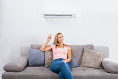 Woman Operating Air Conditioner With Remote Control. Young Happy Woman Sitting On Couch Operating Air Conditioner With Remote Control At Home Stock Images