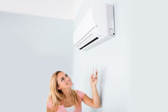 Woman Operating Air Conditioner With Remote. Portrait Of A Happy Woman Holding Remote Control In Front Of Air Conditioner At Home Stock Photography
