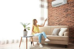 Woman operating air conditioner while sitting on sofa. At home stock photography