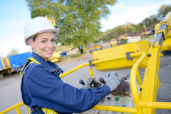 Woman operating controls cherry picker bucket. Woman operating controls of cherry picker bucket stock images
