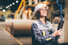 Woman operating crane. At paper mill factory Royalty Free Stock Photos