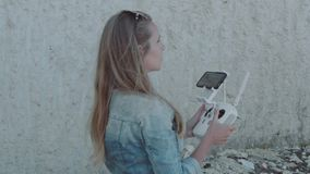 Woman operating drone with remote controller. While standing near beautiful white cliffs during sunny summer day - video in slow motion stock video