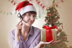 Woman operator on Christmas back with present Royalty Free Stock Images