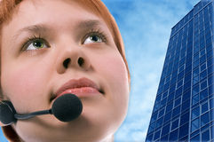 Woman operator with headphoneson blue sky and business buildings Royalty Free Stock Photography