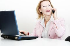 Woman operator phone with laptop. Close up of a smiling woman at work place Royalty Free Stock Images