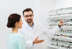 Woman and optician showing glasses at optics store Stock Photography