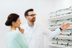 Woman and optician showing glasses at optics store Royalty Free Stock Photo