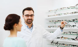 Woman and optician showing glasses at optics store Stock Images