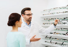 Woman and optician showing glasses at optics store Royalty Free Stock Images