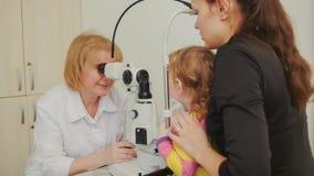 Woman optometrist checks eyesight at little girl - child`s ophthalmology Royalty Free Stock Images