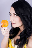 Woman with orange. Portrait of a beautiful young woman eating an orange Stock Photos
