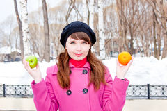 Woman  with orange and apple in hands Royalty Free Stock Photos
