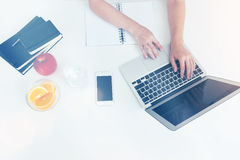 Woman with orange and apple typing. Woman hands typing at her laptop keyboard. Apple, orange, stack of phone books and smart phone are on her desk. Concept of Stock Image
