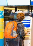 TOKYO, JAPAN - NOVEMBER 7, 2017: Woman with orange backpack at the airport check-in counter. Back view. With selective focus royalty free stock image