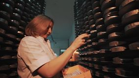 Woman with orange box walks to rack with stacks of metal discs. Caucasian woman in white robe with orange box walks to rack with stacks of metal discs at stock footage