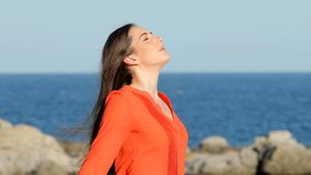 Woman in orange breathing fresh air on the beach stock video