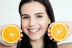 Woman with orange close-up face. Beautiful women exists to clean skin on the face. Asian woman. Royalty Free Stock Image
